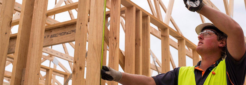 builder measuring timber frame