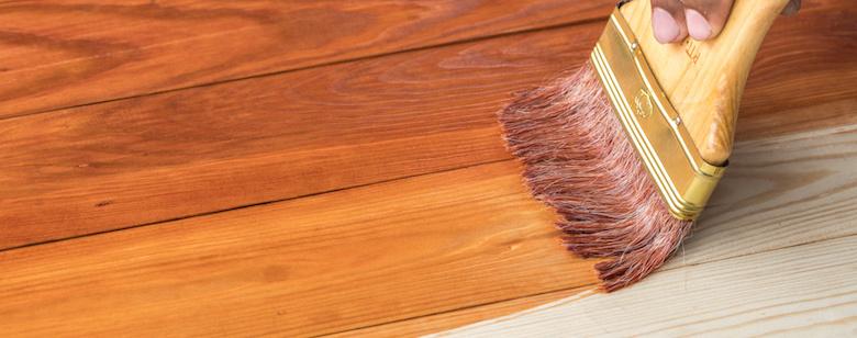 hand holding a brush applying varnish paint on treated pine