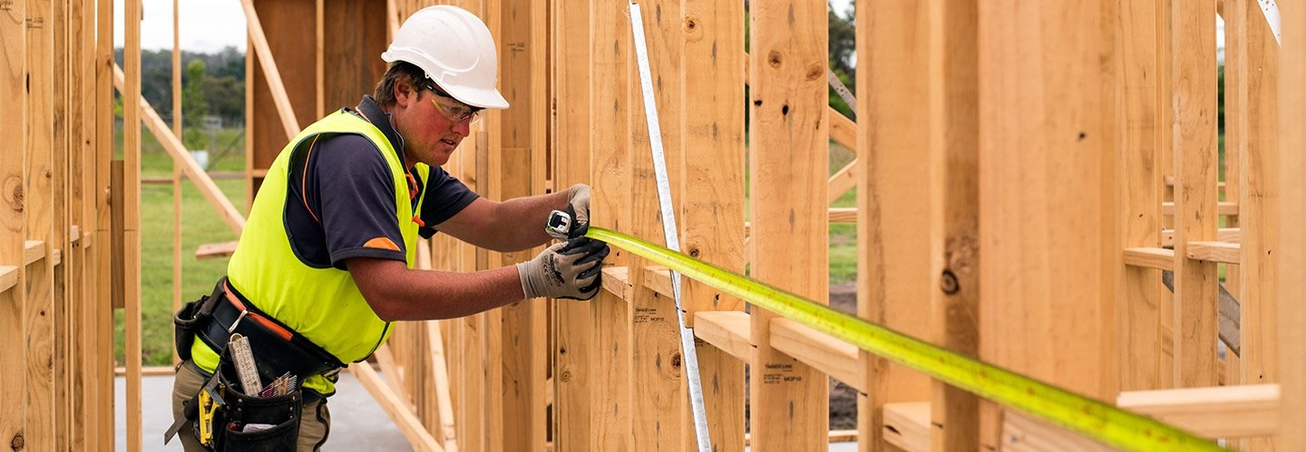 tradie measuring timber frame
